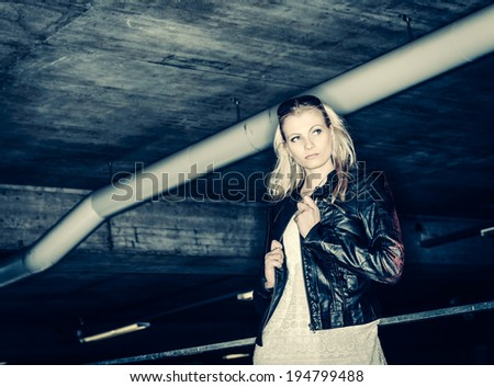 Beautiful self-confident urban girl spend some time in a concrete building, cross processed image - stock photo