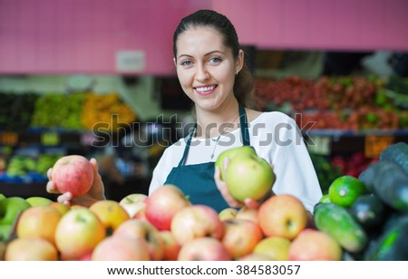 Beautiful sellers apples stacked on the counter and smiling