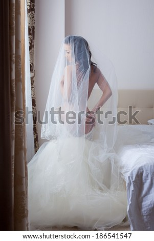 Beautiful seminude bride posing in hotel room