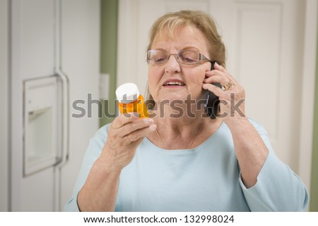 Beautiful Senior Adult Woman in Kitchen on Her Cell Phone Holding Prescription Bottle. - stock photo