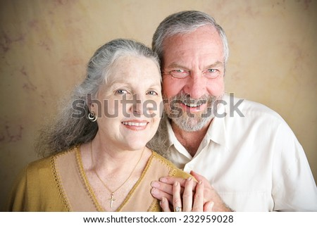 Beautiful senior Christian couple.  She is wearing a cross and wedding.  Portrait illustrating traditional family values.  Slight vignette added for emphasis.   - stock photo