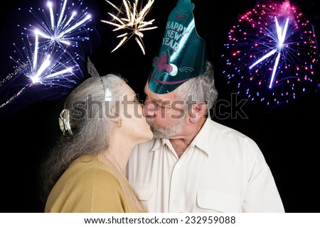 Beautiful senior couple at a New Year's party kisses at the stroke of midnight as the fireworks go off in the background.   - stock photo