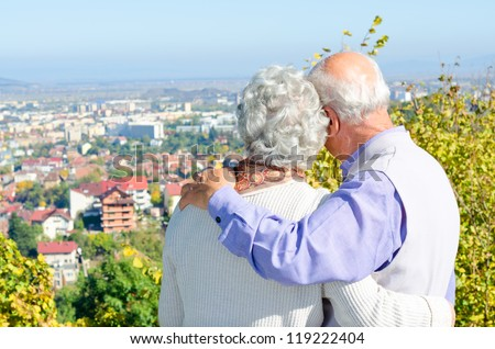 Beautiful senior couple looking to the city - stock photo