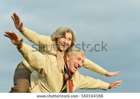 Beautiful senior couple on the background of sky - stock photo