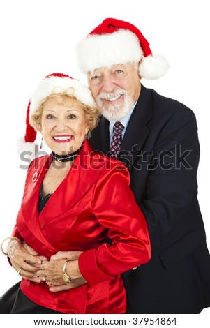 Beautiful senior couple posing for a Christmas portrait in their Santa hats.  Isolated on white. - stock photo