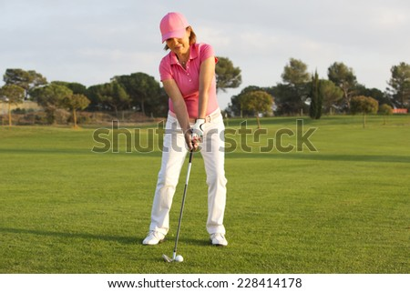 beautiful senior female golf player on a golf course - stock photo