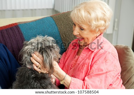Beautiful senior lady pats her adorable mixed breed dog. - stock photo