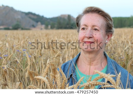 Beautiful senior natural woman sitting in wheat and enjoying with copy space