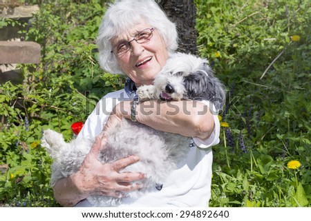 beautiful Senior smiling woman hugging her dog in the summer mountain - stock photo