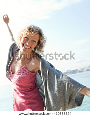 Beautiful senior tourist woman dynamic by transparent blue sea on holiday, joyful smiling looking at camera playful with open arms on holiday, coastal outdoors. Healthy lifestyle, nature exterior. - stock photo
