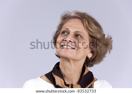 Beautiful senior woman looking up (isolated on gray) - stock photo