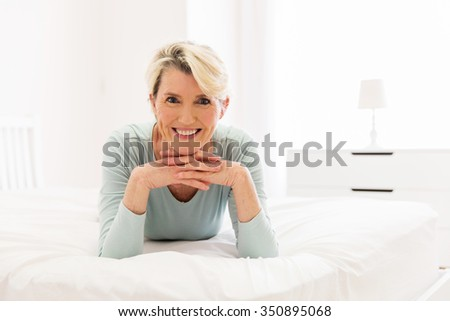beautiful senior woman lying on bed - stock photo