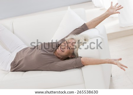 beautiful senior woman relaxing at home in her bed arm  up and stretching - stock photo