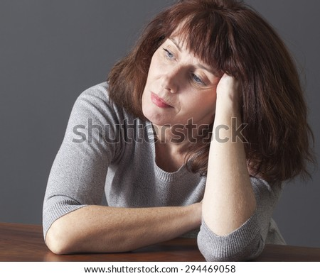 beautiful senior woman resting her face on her hands laying down on a table in reflection about aging - stock photo