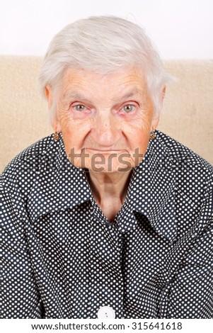 Beautiful senior woman sitting on a sofa - stock photo