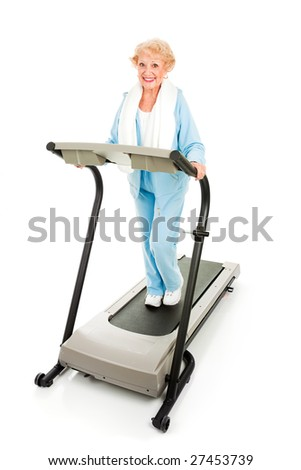 Beautiful senior woman stays fit by exercising on a treadmill.  Isolated on white.