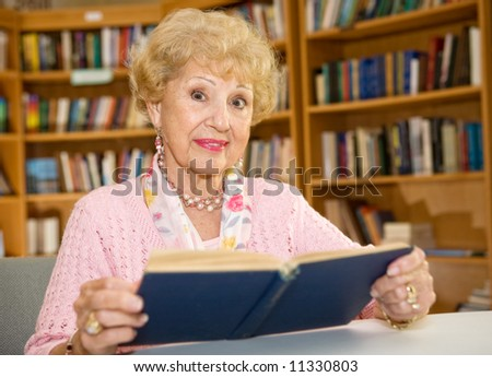 Beautiful senior woman studying in the library.