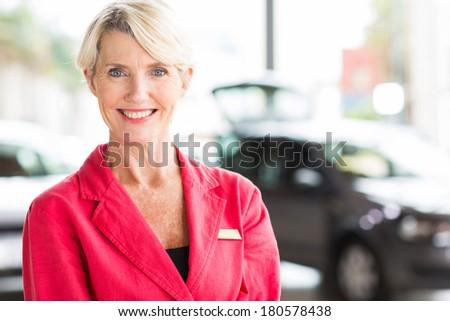 beautiful senior woman working at car dealership - stock photo