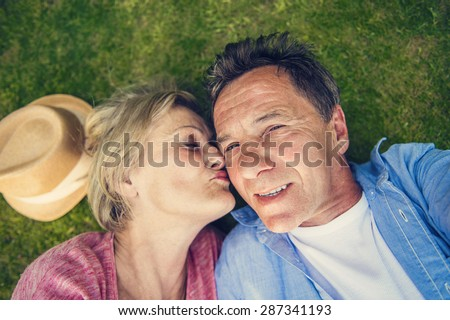 Beautiful seniors lying on a grass in a park taking selfie