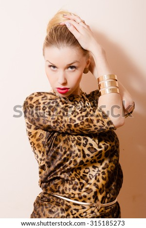 Beautiful sensual blond lady in leopard print touching hair