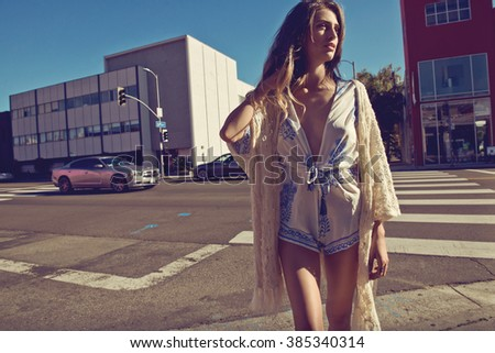 beautiful sensual blonde woman posing in the street in summer jumpsuit and lace pareo. Fashion photo