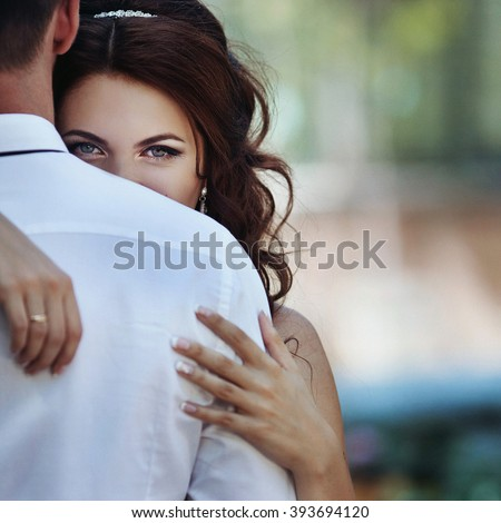 Beautiful sensual bride hugging handsome groom closeup - stock photo