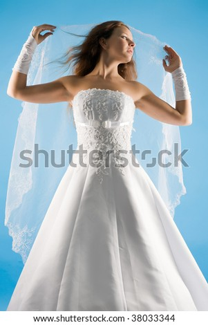 beautiful sensual bride in a wedding dress and with a veil on a blue background