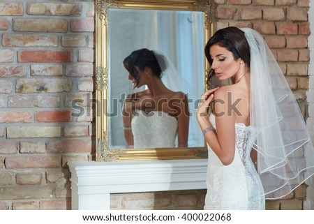 Beautiful, sensual bride standing front of mirror in wedding dress and veil. - stock photo