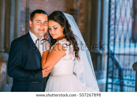 Beautiful sensual brunette bride and handsome groom at sunset castle balcony. Newlyweds near columns and old door embracing and posing kissing picture.