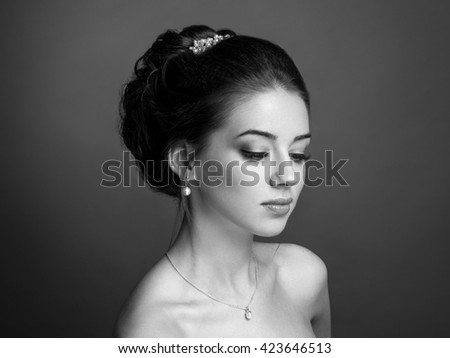 Beautiful sensual brunette with elegant hairstyle. Wedding accessories. Fashion photo