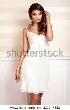 Beautiful sensual brunette woman posing in elegant room in nightwear - stock photo