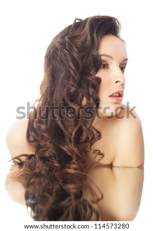 Beautiful sensual brunette woman with long wavy hairs and reflection - isolated on white