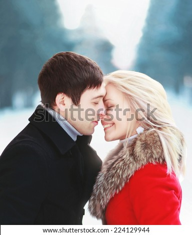 Beautiful sensual couple in love in cold winter day, gentle kiss moment. Christmas, love, relationships and people concept - stock photo