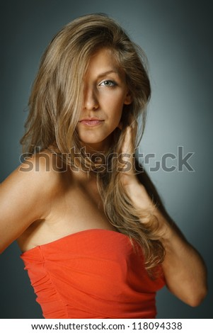 Beautiful sensual female in coral red dress. Shallow deep of field. - stock photo