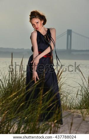 Beautiful sensual girl in elegant black dress posing on the beach. - stock photo