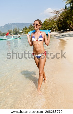 Beautiful sensual lady in blue and white striped bikini with penny board smiles and splashes water with her leg