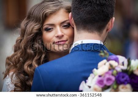 Beautiful sensual newlywed bride hugging handsome groom face closeup - stock photo