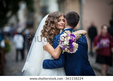 Beautiful sensual newlywed bride hugging handsome groom face while holding bouquet - stock photo