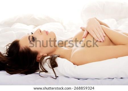 Beautiful sensual topless woman lying on bed. - stock photo