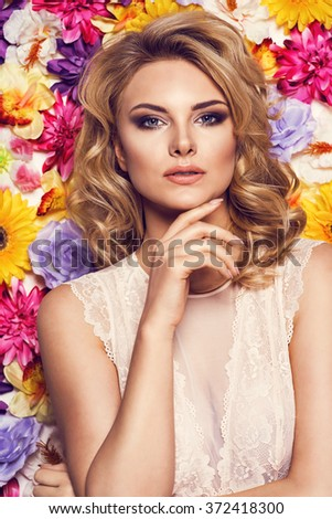Beautiful sensual woman in laced lingerie on colorful wall of flowers. Beauty photo, nice hair - stock photo