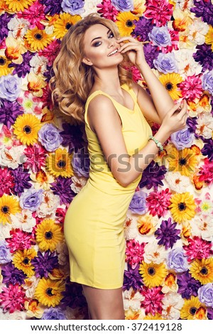 Beautiful sensual woman in yellow dress and bracelet on colorful wall of flowers. Fashion photo, nice hair - stock photo