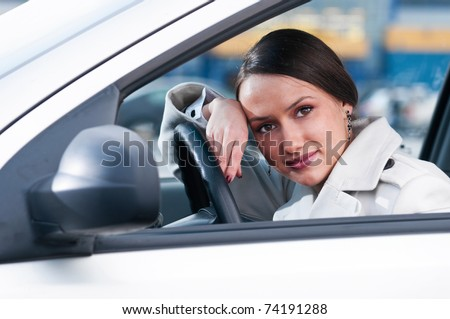 beautiful sensual woman put her head on steering wheel and looking at camera - stock photo
