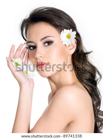 Beautiful sensual woman with fresh clean skin of the face and flowers in hands - white background