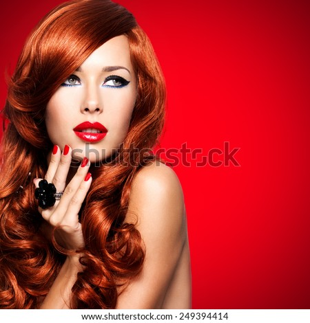 Beautiful sensual woman with long red hairs and red nails on red background - stock photo