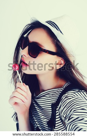 Beautiful sensual young brunette woman in a hat with candy in studio, lifestyle - stock photo