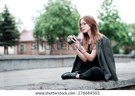 beautiful sensual young hipster girl in glasses with a camera in hand