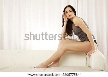 Beautiful sensuality and attractive sexy female young adult brunette woman posing in grey shirt on the white sofa