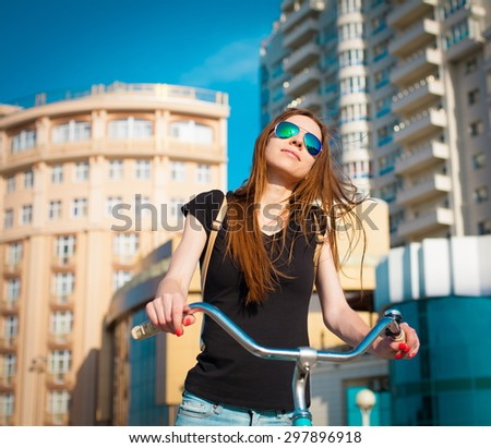 beautiful sensuality elegance brown hair woman happy fun cheerful smiling blue sunglasses black t-shirt jeans bicycle urban city portrait nature slim sport body hobby equipment riding bike cyclist  - stock photo