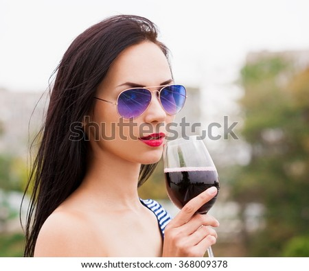 Beautiful sensuality elegance brunette hair woman, has happy fun cheerful smiling face, blue sunglasses, sexy slim body, striped dress, red wine. Portrait urban city. Sunny day. - stock photo