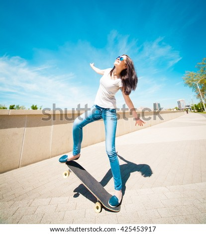 Beautiful sensuality elegance brunette hair woman, has happy fun cheerful smiling face, white t-shirt, blue jeans, long legs, holding skateboard. Has slim sport body. Portrait urban city.